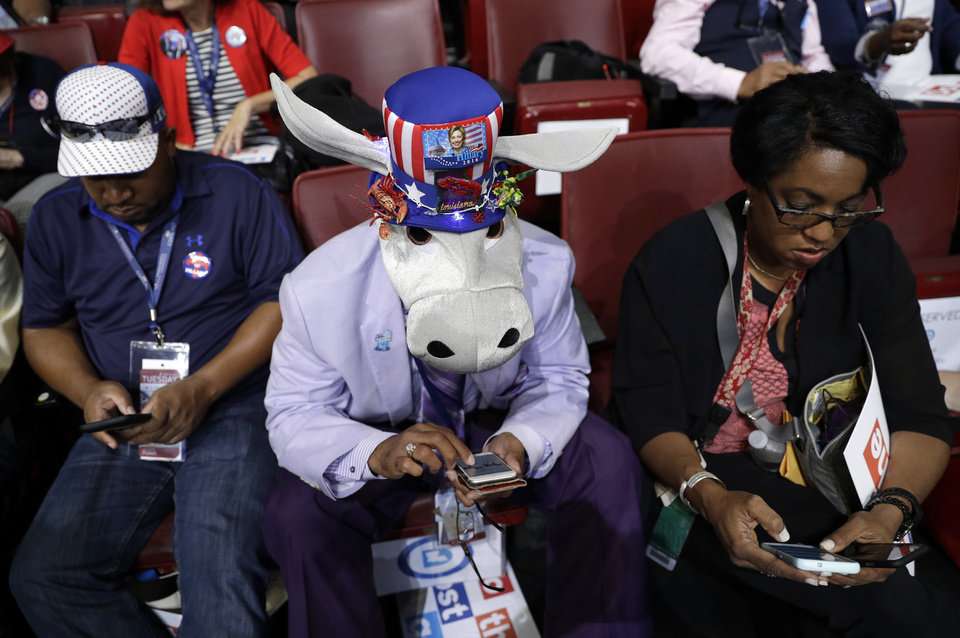 Photo - Rodney McFarland Sr.,wears a donkey hat as he check his phone before the start of the second day session of the Democratic National Convention in Philadelphia, Tuesday, July 26, 2016. (AP Photo/John Locher)
