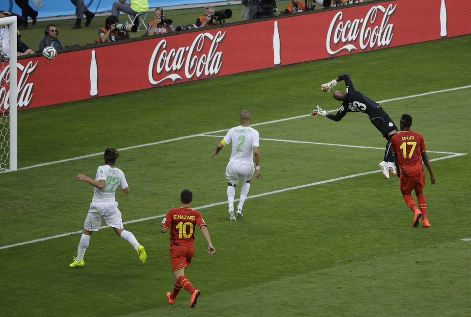 Photo - The ball kicked by Belgium's Dries Mertens goes into the net past Algeria goalkeeper Cedric Si Mohamed during the group H World Cup soccer match between Belgium and Algeria at the Mineirao Stadium in Belo Horizonte, Brazil, Tuesday, June 17, 2014.  From left Algeria's Mehdi Mostefa, Belgium's Eden Hazard and Belgium's Divock Origi. (AP Photo/Sergei Grits)