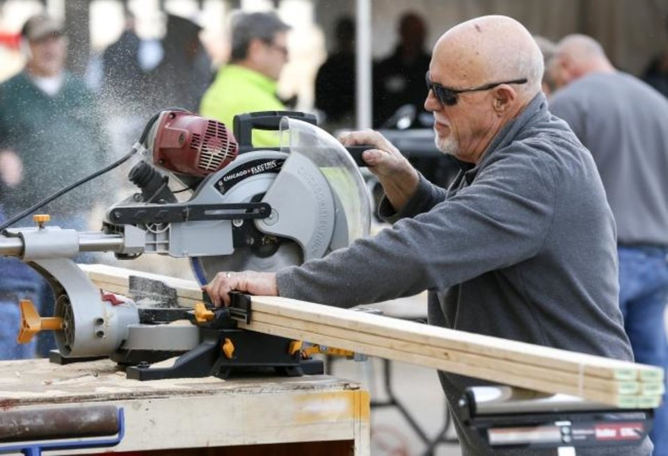 Photo -  Bill Morgan saws pieces of wood during the Royal Family Kids'
