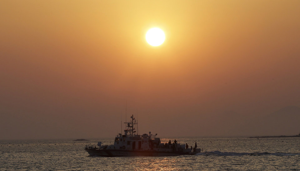 Photo - A South Korean Coast Guard ship sails at sunset near a port where relatives wait for news on their loved ones believed to have been trapped in the sunken ferry Sewol in Jindo, south of Seoul, South Korea, Tuesday, April 22, 2014. One by one, coast guard officers carried the newly arrived bodies covered in white sheets from a boat to a tent on the dock of this island, the first step in identifying a sharply rising number of corpses from a South Korean ferry that sank nearly a week ago. (AP Photo/Lee Jin-man)