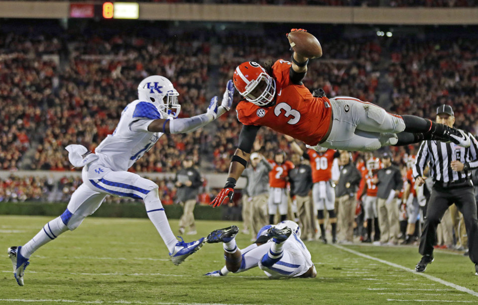 Photo - FILE - In this Nov. 23, 2013, file photo, Georgia running back Todd Gurley (3) dives into the end zone for a touchdown as Kentucky cornerback Jaleel Hytchye, left, defends in the first half of an NCAA college football game in Athens, Ga. Fully healthy again, this bulldog of a Bulldog _ 6-foot-1, 226 pounds _ has his eyes set on a 2,000-yard season and possibly a spot in New York. (AP Photo/John Bazemore, File)