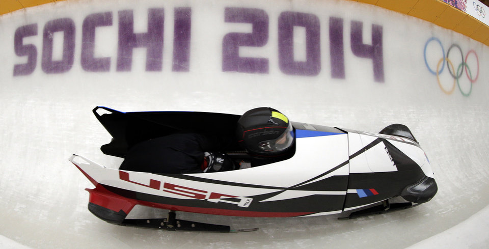 Photo - Jazmine Fenlator and Lolo Jones of the United States take a turn during a training session for the women's bobsleigh at the 2014 Winter Olympics,  Sunday, Feb. 16, 2014, in Krasnaya Polyana, Russia. (AP Photo/Michael Sohn)