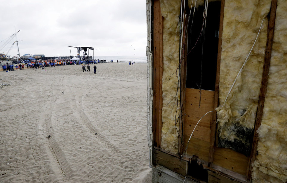 Photo - The insulation of a restroom on the Seaside Heights boardwalk is visible as people gather near a stage during a performance by musical group Fun, Friday, May 24, 2013, in Seaside Heights, N.J. New Jersey Gov. Chris Christie cut a ribbon to symbolically reopen the state's shore for the summer season, seven months after being devastated by Superstorm Sandy. Several beach communities have annual beach ribbon cuttings, announcing they are back in business. But this year's ceremonies are more poignant seven months after a storm that did an estimated $37 billion of damage in the state. (AP Photo/Julio Cortez)