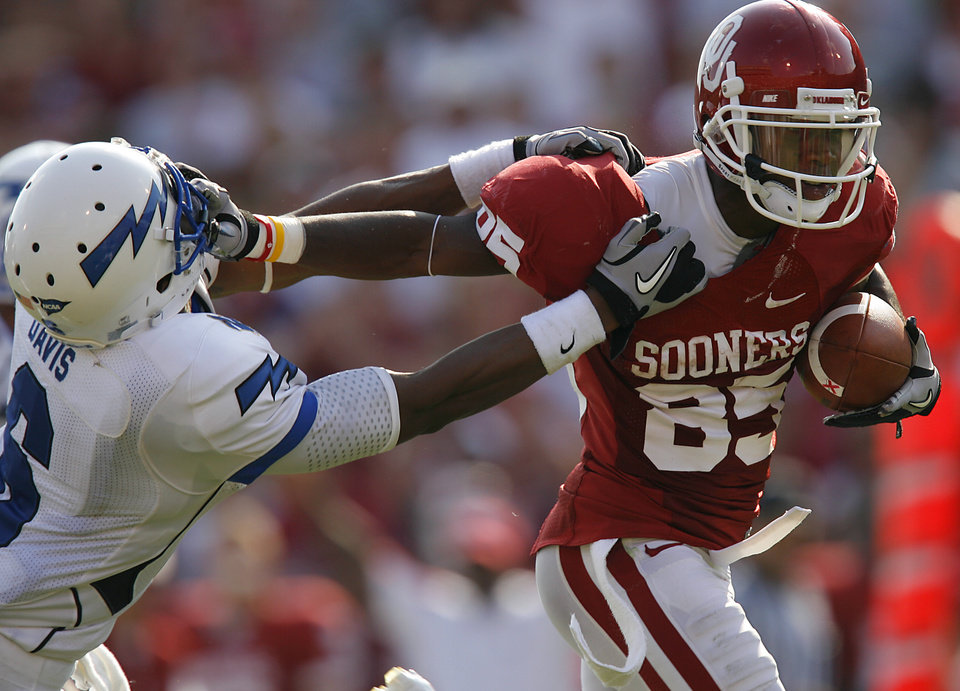 Photo - Oklahoma's Ryan Broyles (85) stiff arms Air Force's Jon Davis (6) after a reception during the second half of the college football game between the University of Oklahoma Sooners (OU) and the Air Force Falcons at the Gaylord Family - Oklahoma Memorial Stadium on Saturday, Sept. 18, 2010, in Norman, Okla.   Photo by Chris Landsberger, The Oklahoman ORG XMIT: KOD