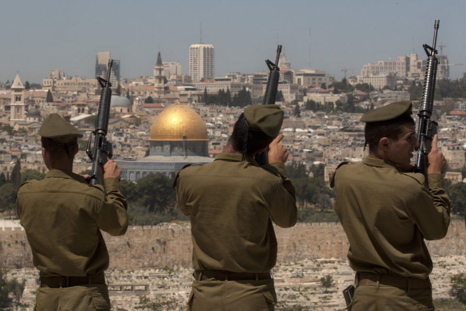 Photo -   Israeli soldiers check their weapons following a Memorial Day ceremony on the Mount of Olives overlooking Jerusalem's Old City, Wednesday, April 25, 2012. (AP Photo/Sebastian Scheiner)
