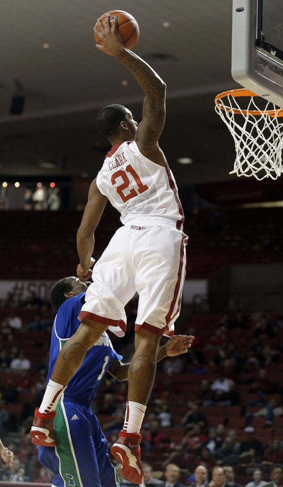 Photo - Oklahoma's Cameron Clark (21) dunks over Texas A&M-CC's Hameed Ali (1) during the men's college game between the University of Oklahoma and the Texas A & M- Corpus Christi at Lloyd Noble Center in Norman, Okla.,  Thursday, Dec. 5, 2013. Photo by Sarah Phipps, The Oklahoman