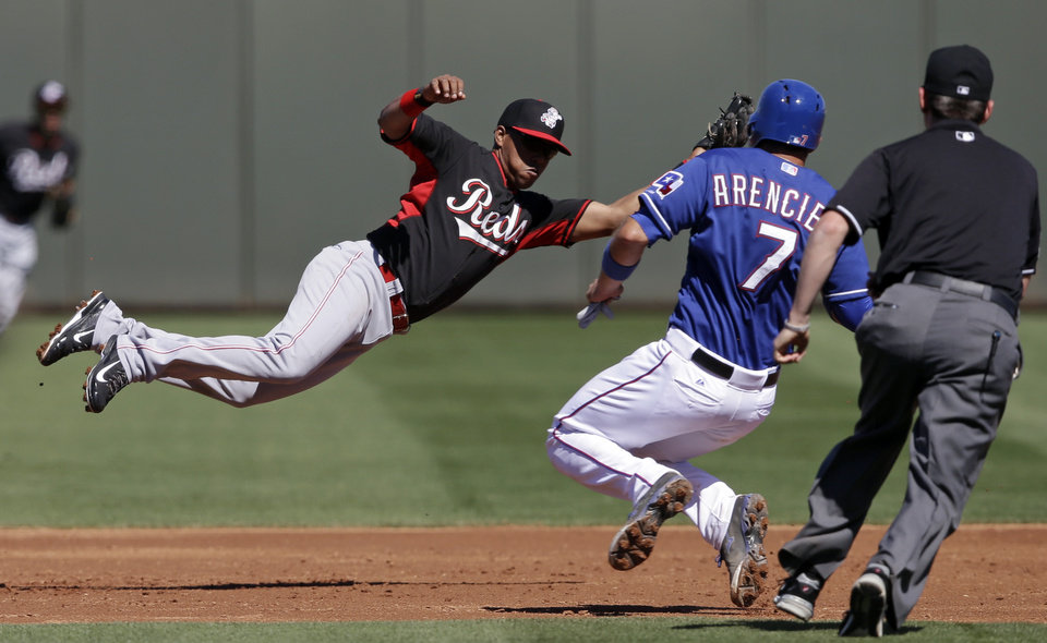 Photo - Cincinnati Reds' Ramon Santiago leaps for a throws as Texas Rangers' J.P. Arencibia steals second during the second inning of a spring exhibition baseball game Monday, March 10, 2014, in Suprise, Ariz. (AP Photo/Darron Cummings)