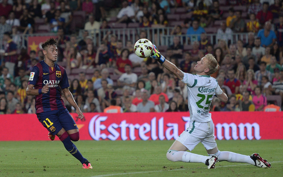Photo - Barcelona's Neymar, from Brazil, left, scores against Leon's goalkeeper Wiliam Yarbrough during the Joan Gamper trophy friendly soccer match at the Camp Nou in Barcelona, Spain, Monday, Aug. 18, 2014. (AP Photo/Manu Fernandez)