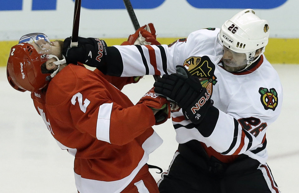 Photo - Chicago Blackhawks center Michal Handzus (26), of the Czech Republic, checks Detroit Red Wings defenseman Brendan Smith (2) during the second period in Game 4 of the Western Conference semifinals in the NHL hockey Stanley Cup playoffs in Detroit, Thursday, May 23, 2013. (AP Photo/Paul Sancya)