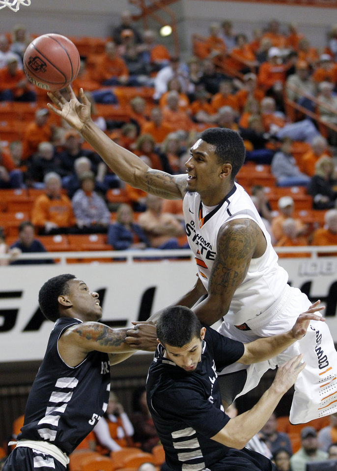 Photo -   Oklahoma State guard Le'Bryan Nash, right, is fouled by Portland State guard Michael Harthun, center, as he goes up for a shot over Harthum and guard Dre Winston, left, in the first half of an NCAA college basketball game in Stillwater, Okla., Sunday, Nov. 25, 2012. (AP Photo/Sue Ogrocki)