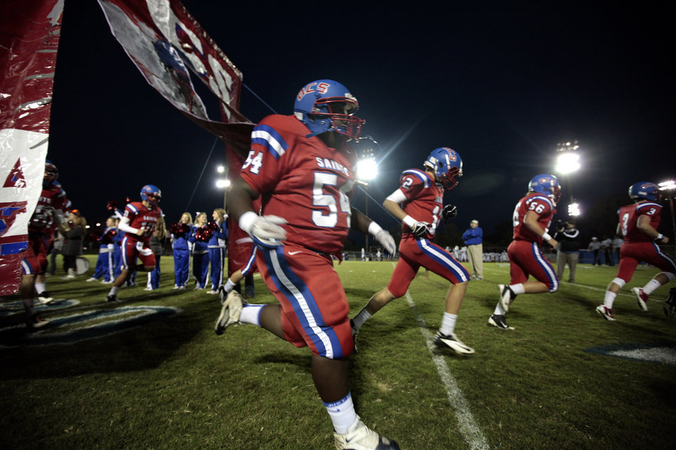Photo - OCS runs onto the field before the high school football game between Oklahoma Christian and Millwood at Oklahoma Christian Schools in Edmond, Okla.,  Friday, Oct. 5, 2012. Photo by Sarah Phipps, The Oklahoman