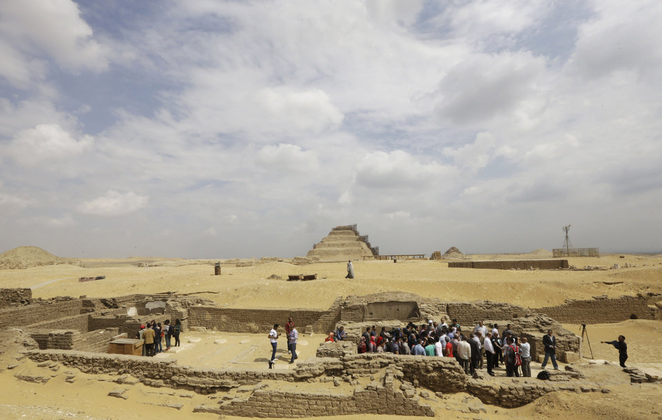 """Photo - Archaeologists and journalists gather at a newly-discovered tomb dating back to around 1100 B.C. at the Saqqara archaeological site, 30 kilometers (19 miles) south of Cairo, Egypt, Thursday, May 8, 2014. Antiquities Minister Mohamed Ibrahim said Thursday that the tomb belongs to a guard of the army archives and royal messenger to foreign countries. Ibrahim says the Cairo University Faculty of Archaeology's discovery at Saqqara adds """"a chapter to our knowledge about the history of Saqqara."""" Saqqara was the necropolis for the ancient Egyptian city of Memphis and site of the oldest known pyramid in Egypt.(AP Photo/Amr Nabil)"""