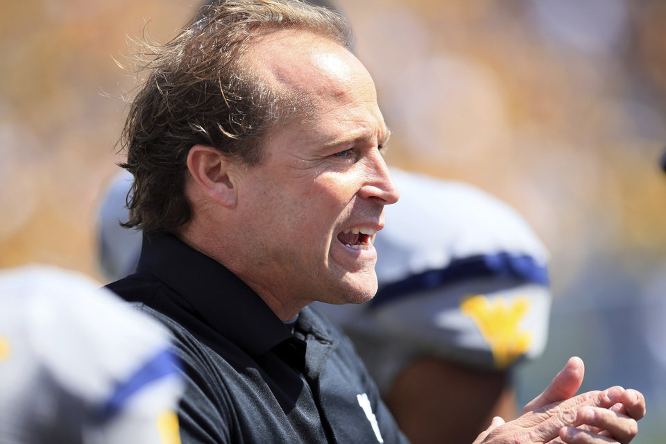 Photo -   West Virginia coach Dana Holgorsen encourages his side during their NCAA college football game against Maryland in Morgantown, W.Va., Saturday, Sept. 22, 2012. WVU won 31-21 (AP Photo/Christopher Jackson)