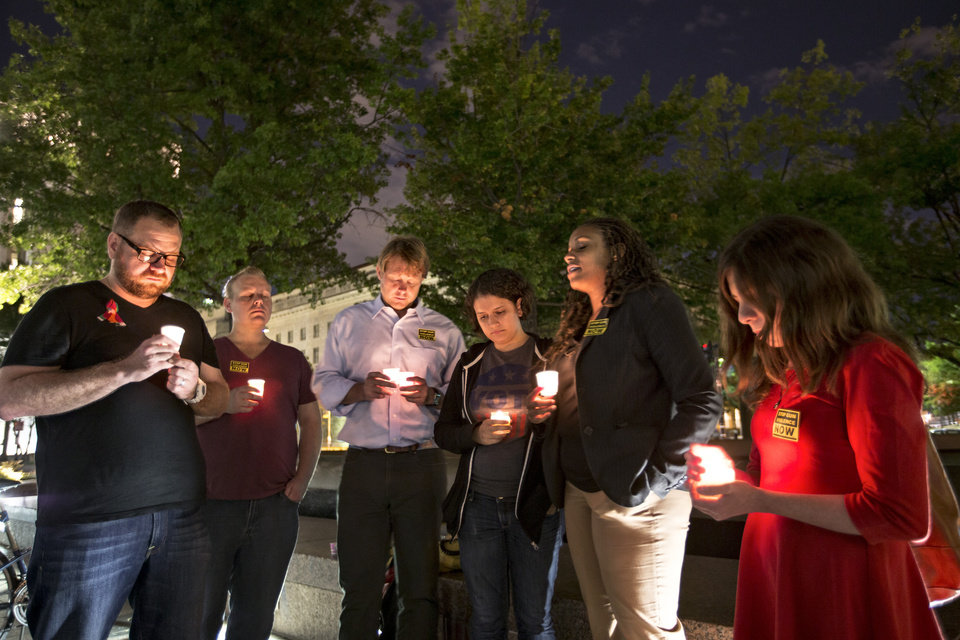 Photo - A small group holds a candle light vigil on Freedom Plaza to remember the victims of the shooting at the Washington Navy Yard, Monday, Sept. 16, 2013, in Washington.  (AP Photo/J. Scott Applewhite)