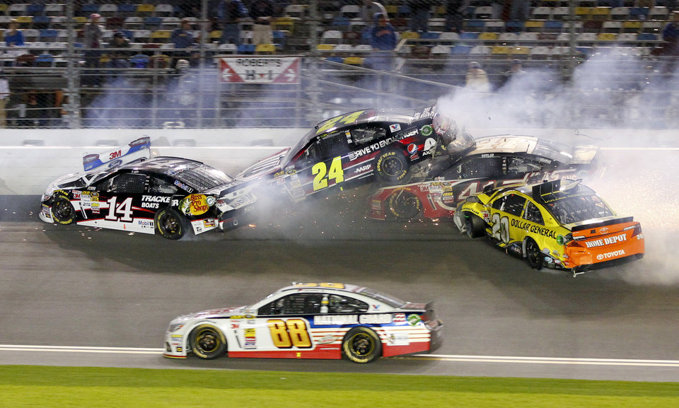 Photo - Tony Stewart (14), Jeff Gordon (24), Kurt Busch, second from right, and Matt Kenseth (20) wreck on the front stretch as Dale Earnhardt Jr. (88) goes low to avoid the crash during the NASCAR Sprint Unlimited auto race at Daytona International Speedway in Daytona Beach, Fla., Saturday, Feb. 15, 2014. (AP Photo/Terry Renna)