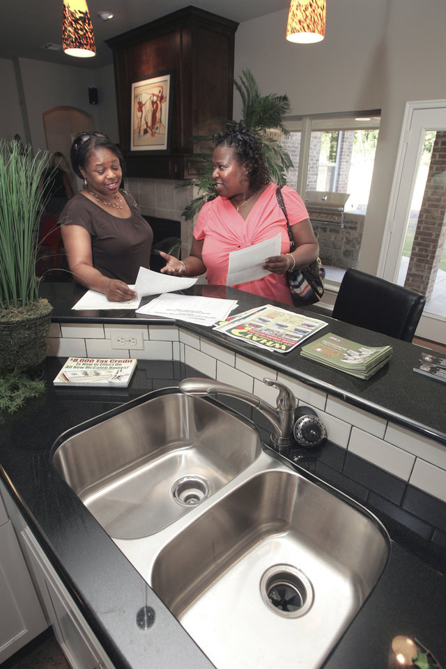 Photo - Cheryl Smith and Vicki Hill look at house plans in a model bungalow by builder Caleb McCaleb in his Arbor Creek addition east of Interstate 35 and north of Second Street in Edmond. Photo by Steve Gooch, THE OKLAHOMAN