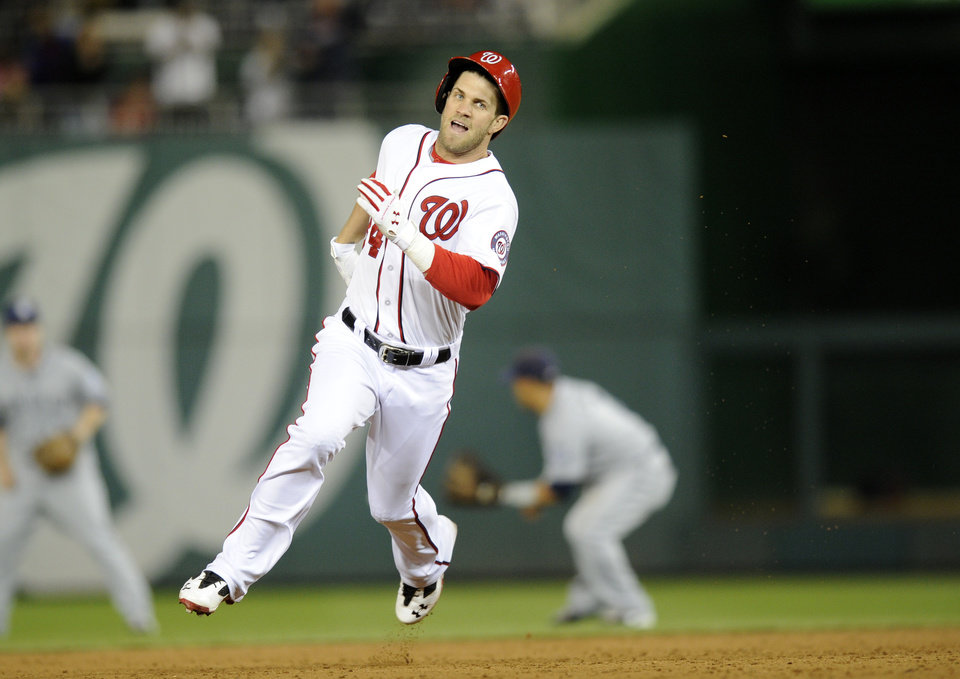 Photo - Washington Nationals left fielder Bryce Harper runs towards third with a three RBI triple during the third inning of a baseball game against the San Diego Padres, Friday, April 25, 2014, in Washington. (AP Photo/Nick Wass)