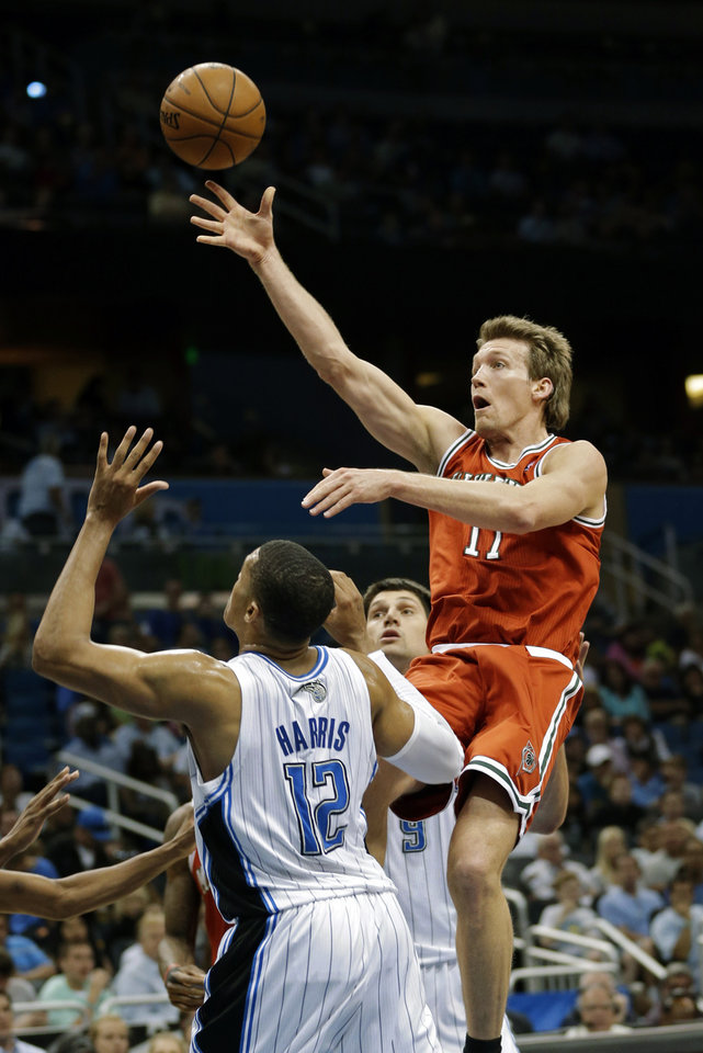 Photo - Milwaukee Bucks' Mike Dunleavy, right, shoots over Orlando Magic's Tobias Harris (12) during the first half of an NBA basketball game, Wednesday, April 10, 2013, in Orlando, Fla. (AP Photo/John Raoux)