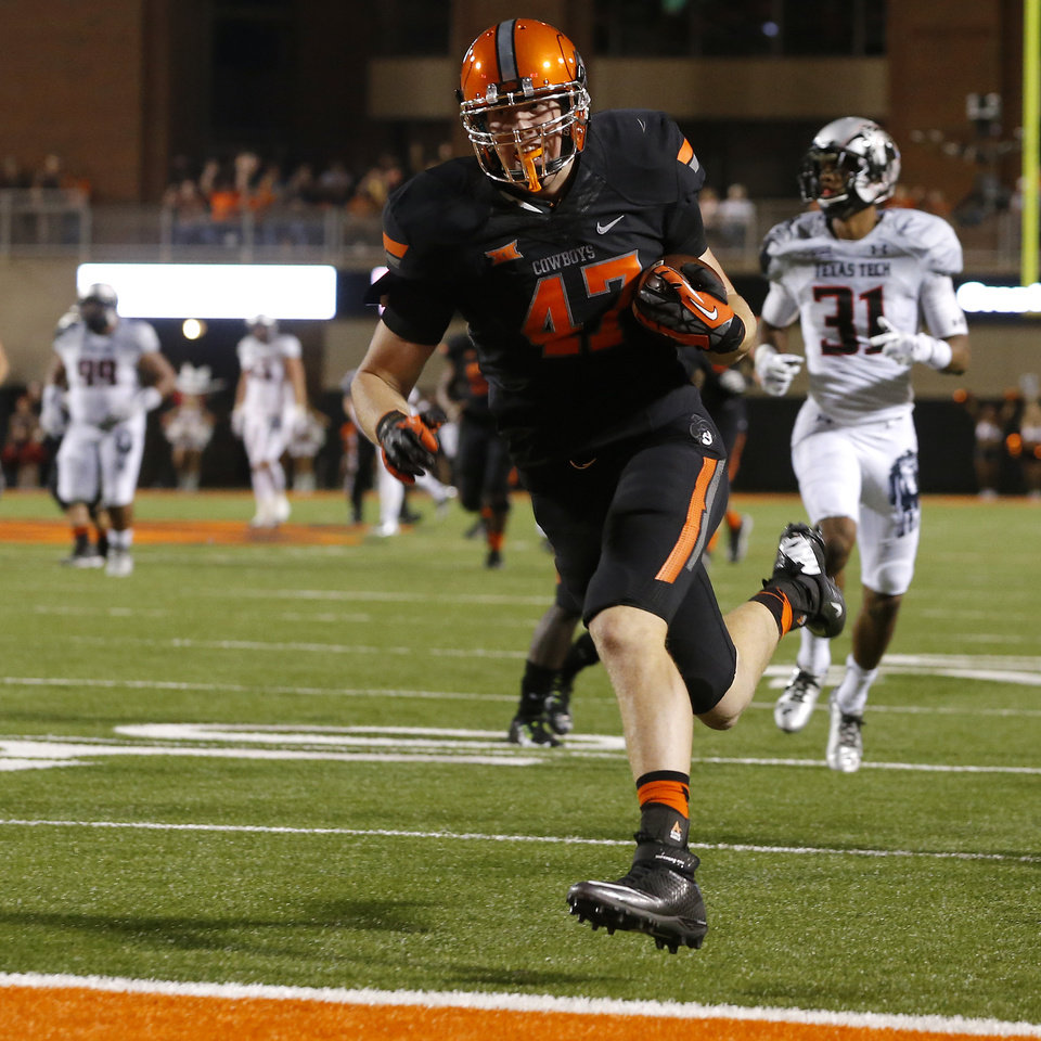 Photo - Oklahoma State's Blake Jarwin (47) scores a touchdown on a reception during a college football game between the Oklahoma State Cowboys (OSU) and the Texas Tech Red Raiders at Boone Pickens Stadium in Stillwater, Okla., Thursday, Sept. 25, 2014. Photo by Bryan Terry, The Oklahoman