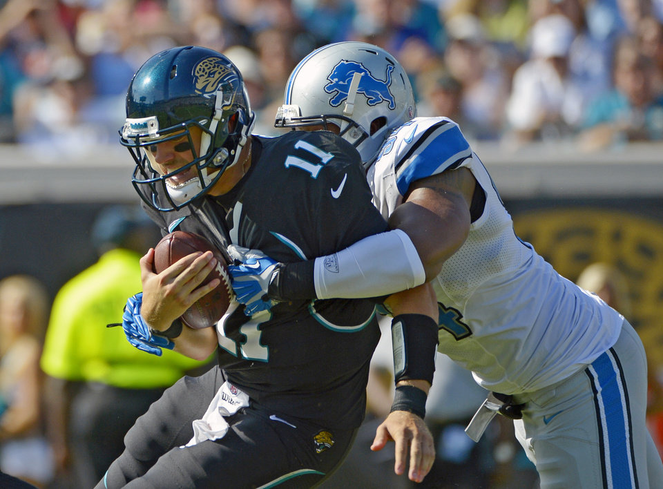 Jacksonville Jaguars quarterback Blaine Gabbert (11) is sacked by Detroit Lions defensive end Lawrence Jackson, right, during the first half of an NFL football game, Sunday, Nov. 4, 2012, in Jacksonville, Fla. (AP Photo/Phelan M. Ebenhack)