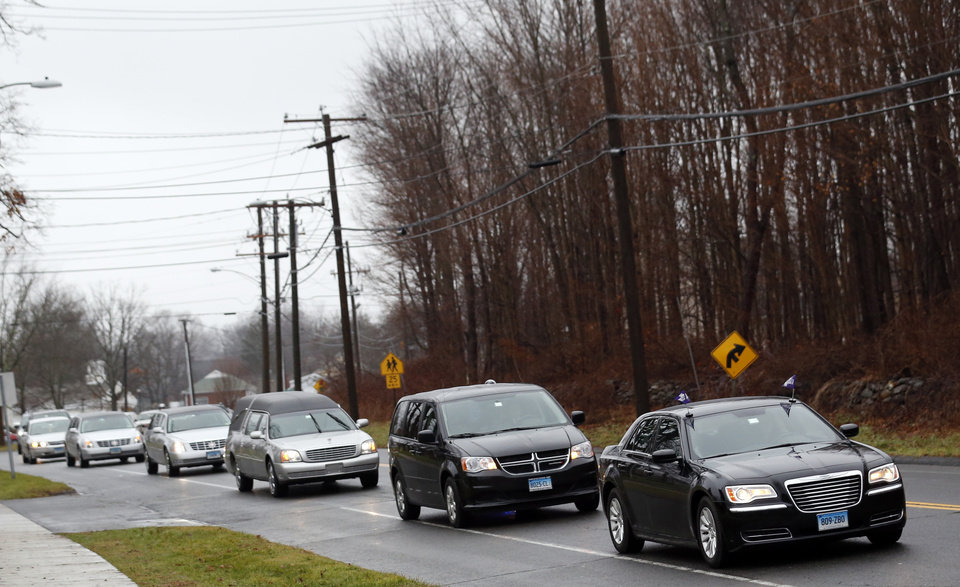 Photo - A procession leads a hearse toward St. Rose of Lima Roman Catholic Church during funeral services for James Mattioli, Tuesday, Dec. 18, 2012, in Newtown, Conn. Mattioli, 6, was killed when Adam Lanza walked into Sandy Hook Elementary School in Newtown, Conn., Dec. 14,  and opened fire, killing 26 people, including 20 children, before killing himself. (AP Photo/Julio Cortez)