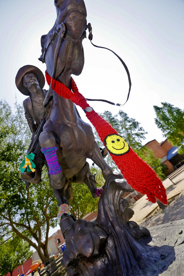 Photo - Knitted art work is attached to the 'Boomer' statue in the Enid town square as part of the Yarnover Enid community art event on Friday, Sept. 6, 2013 in Enid, Okla. The public art project was established to bring the town together to display 'art graffiti' created from items made and donated by the community.  Photo by Chris Landsberger, The Oklahoman