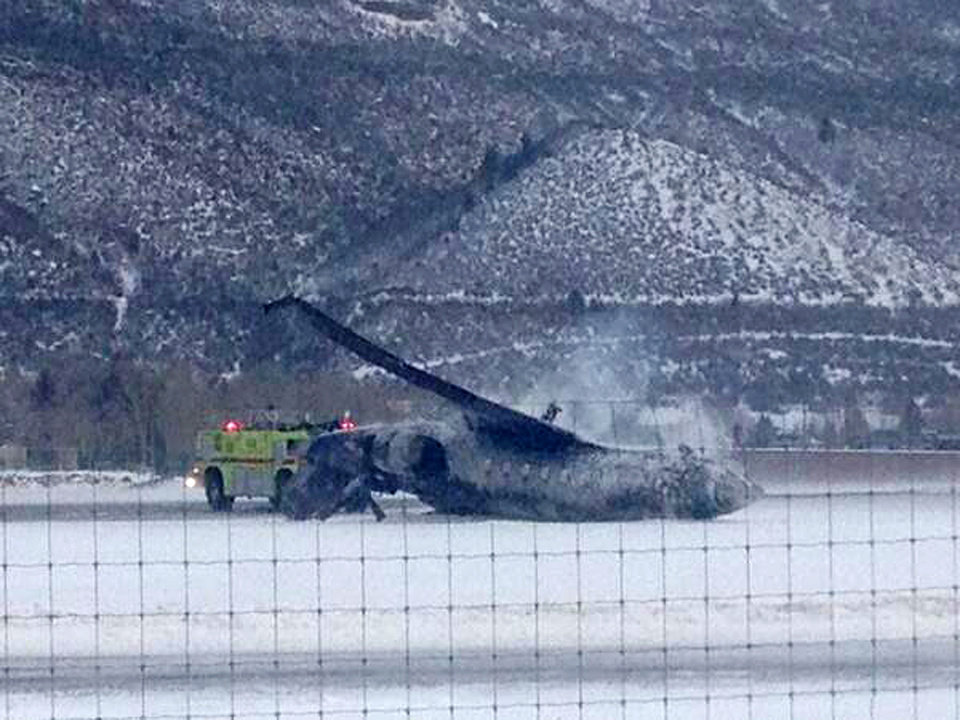 Photo - Emergency crews respond as a small plane lies on a runway at Aspen Airport in western Colorado after it crashed upon landing Sunday, Jan. 5, 2014. Emergency crews are responding to a fiery plane crash at Aspen Airport in western Colorado. (AP Photo/Corey Morris-Singer)