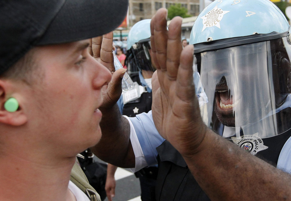 Photo -   A Chicago Police officer confronts a protester during a march and rally at this weekend's NATO summit in Chicago Sunday, May 20, 2012 in Chicago. (AP Photo/Charles Rex Arbogast)