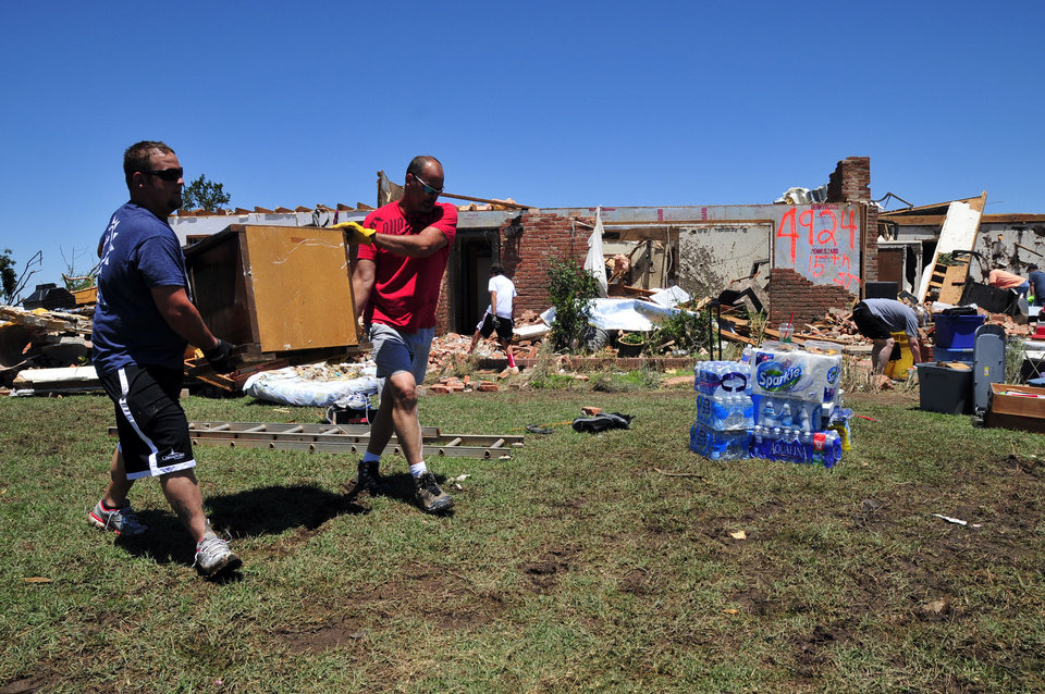 Photo - Josh Stapleton, left, and Dan Garrett help to salvage furniture from their friends Fred and Joann Horn's home that was destroyed by the tornado Saturday, June 1, 2013 in El Reno Okla. (AP Photo/Nick Oxford)