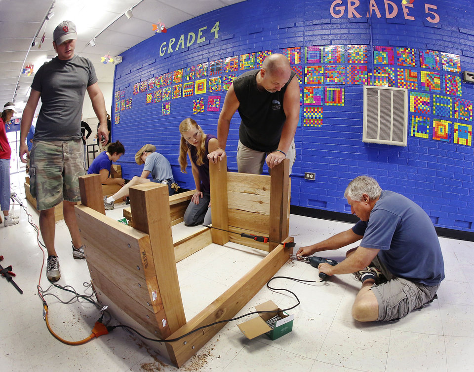 Members of Crossings Community Church build raised garden beds to be installed in the new garden area in Stanley Hupfeld Academy at Western Village's courtyard. Photo by Jim Beckel, The Oklahoman. <strong>Jim Beckel - THE OKLAHOMAN</strong>