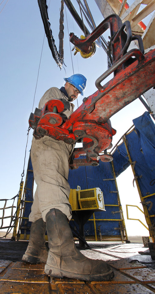 Photo - Floorman Paul Tabarez gets the breakout tongs reedy to pull pipe on a SandRidge oil drilling rig near Medford, Thursday, October 18, 2012. This is for Oklahoma Inc. Photo By David McDaniel/The Oklahoman