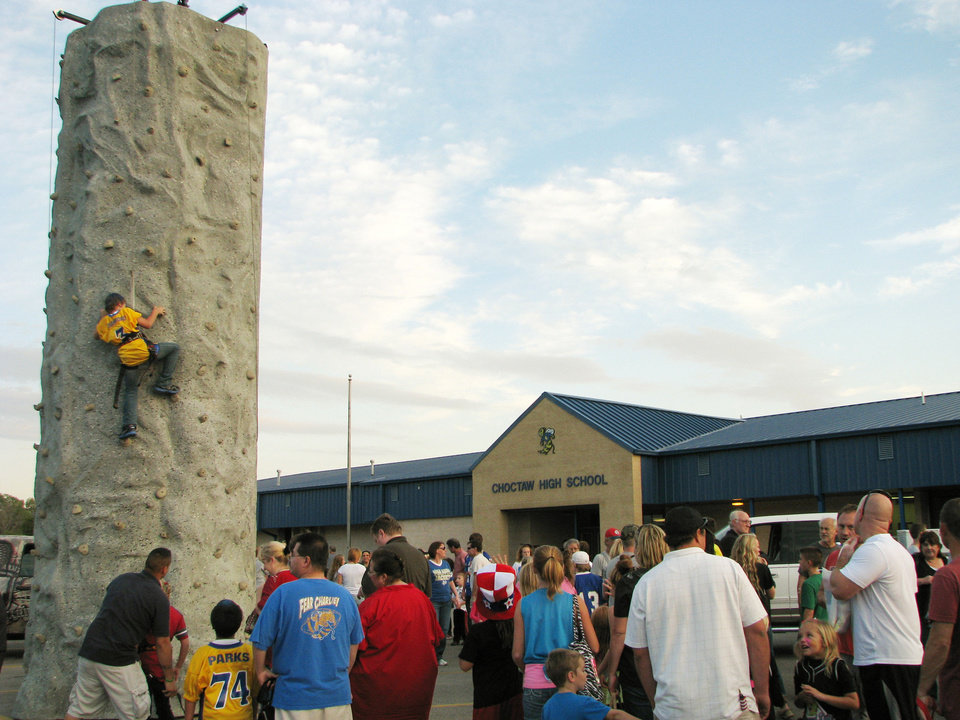 Choctaw High School homecoming festival attendees watch as a boy climbs a rock climbing wall set up in the parking lot. The wall was a popular attraction at the festival on Thursday.