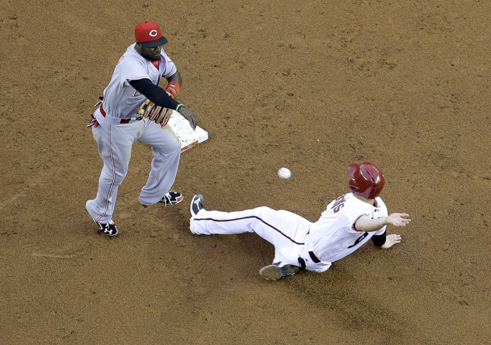 Photo - Cincinnati Reds' Brandon Phillips throws to first after forcing out Arizona Diamondbacks' Tuffy Gosewisch during the second inning of a baseball game, Thursday, May 29, 2014 in Phoenix. Josh Collmenter was out at first. (AP Photo/Matt York)