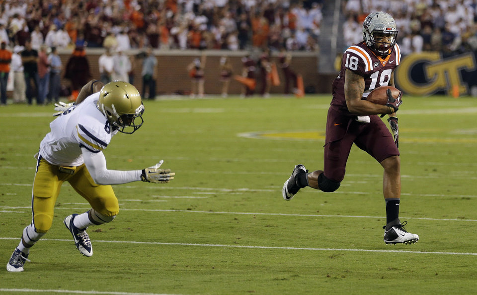 Photo - Virginia Tech wide receiver D.J. Coles (18) outruns Georgia Tech cornerback Louis Young (8) to the end zone for a touchdown in the first half of an NCAA college football game on Thursday, Sept. 26, 2013, in Atlanta. (AP Photo/John Bazemore)