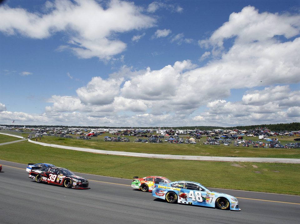 Photo - Driver Jimmie Johnson (48) holds on to the lead in the early laps  of an NASCAR Sprint Cup Series auto race, Sunday Aug. 4, 2013, at Pocono Raceway in Long Pond, Pa. (AP Photo/Mel Evans)