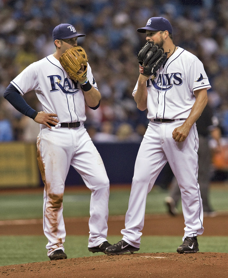 Photo - Tampa Bay Rays third baseman Evan Longoria talks with starting pitcher Erik Bedard, right, as Bedard waits on the mound to be pulled during the fourth inning of a baseball game against the New York Yankees on Friday, April 18, 2014, in St. Petersburg, Fla. (AP Photo/Steve Nesius)
