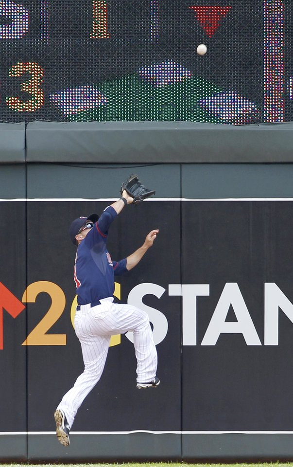 Photo - Minnesota Twins center fielder Sam Fuld goes up the wall to catch a flyout to center by New York Yankees' Jacoby Ellsbury during the first inning of a baseball game in Minneapolis, Sunday, July 6, 2014. (AP Photo/Ann Heisenfelt)
