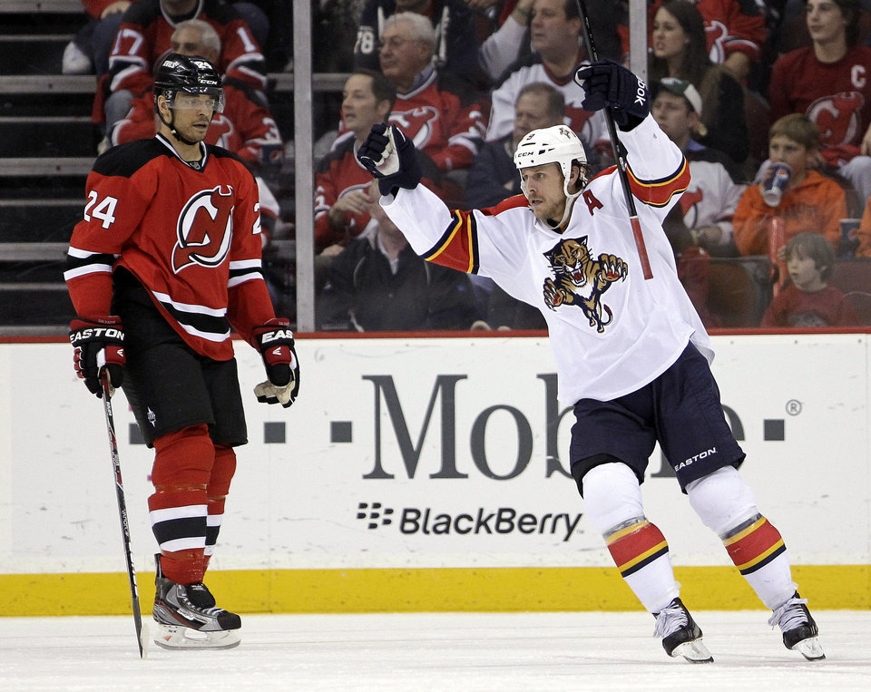 Photo -   Florida Panthers' Stephen Weiss, right, celebrates a goal scored by Kris Versteeg as New Jersey Devils' Bryce Salvador skates by during the second period of Game 6 of a first-round NHL hockey Stanley Cup playoff series, Tuesday, April 24, 2012, in Newark, N.J. (AP Photo/Julio Cortez)