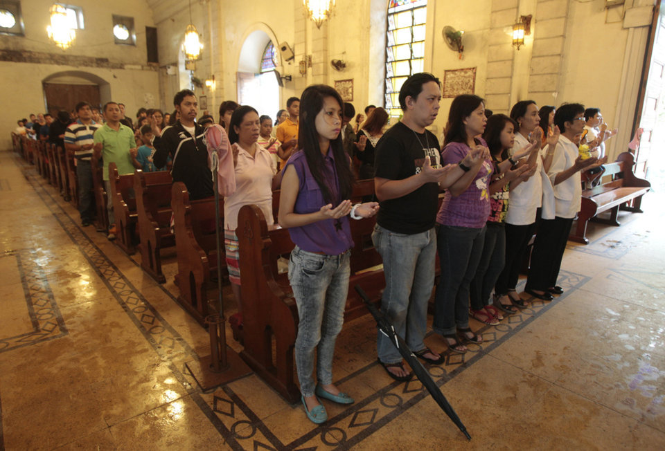 "CORRECTS MONTH - Filipino Catholics offer prayers during a mass at the Our Lady of Remedies Parish Church in Manila, Philippines Sunday, Sept. 22, 2013. Catholics around the globe are expressing mixed but mostly positive reactions to Pope Francis' recent remarks that the church has become too focused on ""small minded rules"" on hot-button issues like homosexuality and abortion. (AP Photo/Aaron Favila)"