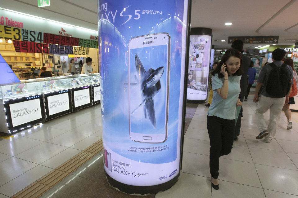 Photo - A woman passes by a billboard of  Samsung Electronics Co.'s Galaxy 5 at a subway station in Seoul, South Korea, Tuesday, July 8, 2014. Samsung Electronics Co. said operating profit declined to a two-year low in the second quarter, hit by the strong local currency and slowing demand for smartphones in China.(AP Photo/Ahn Young-joon)