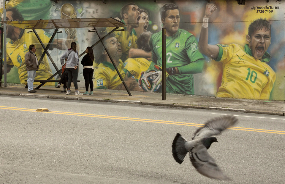 Photo - A mural of Brazilian soccer player Neymar, right, and others cover a wall by a bus stop in Sao Paulo, Brazil, Monday, May 26, 2014. The mural was painted by Brazilian street artist Rodolfo Turini ahead of the World Cup soccer tournament that starts in June. (AP Photo/Andre Penner)