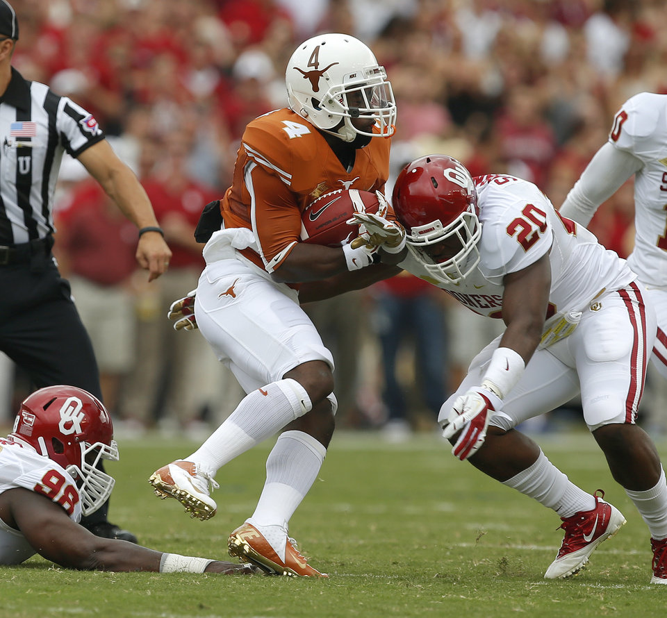 Photo - UT's Daje Johnson (4) runs between OU's Chuka Ndulue (98) and Frank Shannon (20) during the Red River Rivalry college football game between the University of Oklahoma Sooners and the University of Texas Longhorns at the Cotton Bowl Stadium in Dallas, Saturday, Oct. 12, 2013. Texas won 36-20. Photo by Bryan Terry, The Oklahoman
