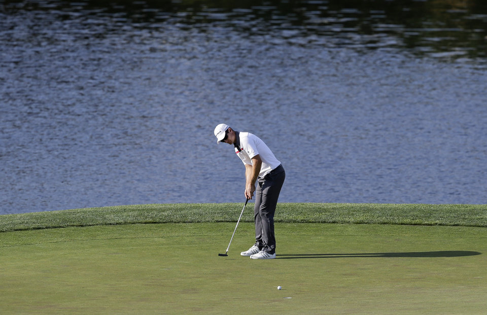 Photo - Justin Rose, of England, putts on the 18th fairway during the final round of the Quicken Loans National PGA golf tournament, Sunday, June 29, 2014, in Bethesda, Md. After a bogey on 18, Rose went on to beat Shawn Stefani in a playoff round. (AP Photo/Patrick Semansky)