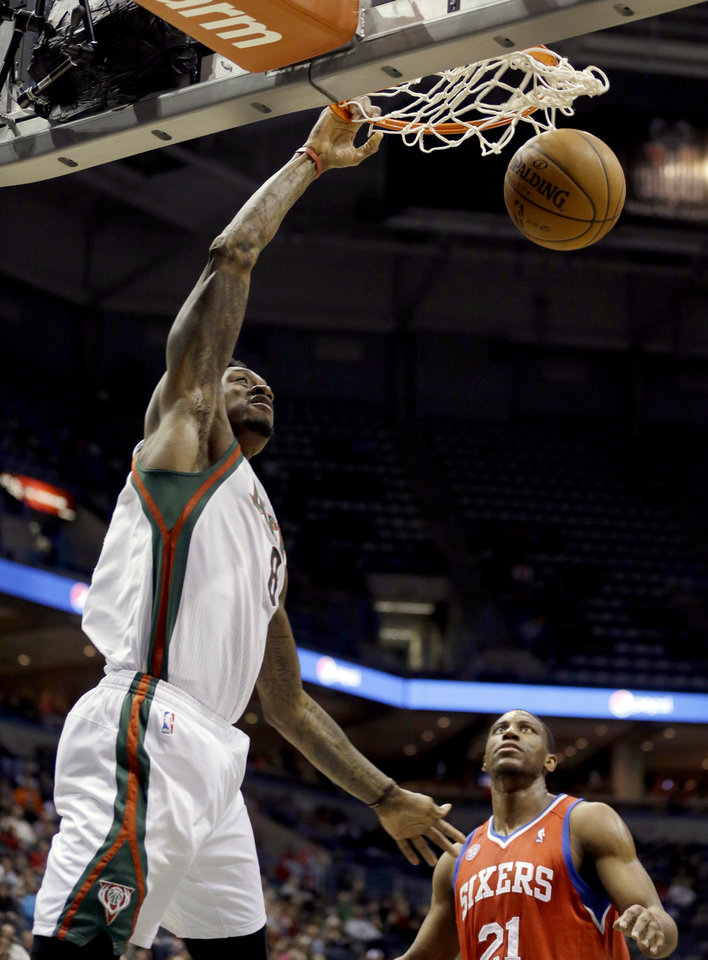 Photo - Milwaukee Bucks' Larry Sanders, left, dunks in front of Philadelphia 76ers' Thaddeus Young (21) during the second half of an NBA basketball game, Tuesday, Jan. 22, 2013, in Milwaukee. The Bucks won 110-102. (AP Photo/Jeffrey Phelps)
