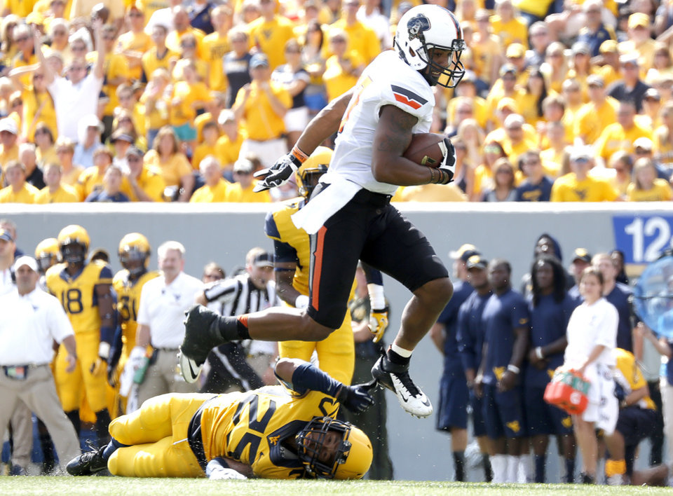 Photo - Oklahoma State's Tracy Moore (87) leaps over West Virginia's Darwin Cook (25) as he scores a touchdown during a college football game between the Oklahoma State University and West Virginia University on Mountaineer Field at Milan Puskar Stadium in Morgantown, W. Va.,   Saturday, Sept. 28, 2013. Photo by Sarah Phipps, The Oklahoman