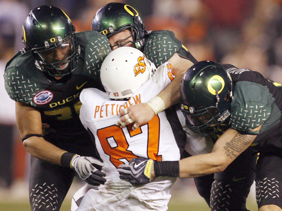 Photo - OSU's Brandon Pettigrew (87) is taken down by a gang of Oregon defenders in the fourth quarter of the Holiday Bowl college football game between Oklahoma State and Oregon at Qualcomm Stadium in San Diego, Tuesday, Dec. 30, 2008. Oregon won, 42-31. PHOTO BY NATE BILLINGS, THE OKLAHOMAN