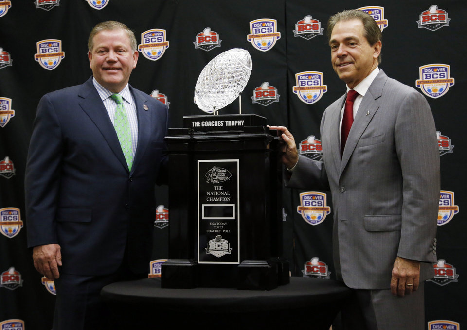 Photo - Alabama head coach Nick Saban and Notre Dame head coach Brian Kelly pose with The Coaches' Trophy during a news conference for the BCS National Championship college football game Sunday, Jan. 6, 2013, in Miami. (AP Photo/John Bazemore)