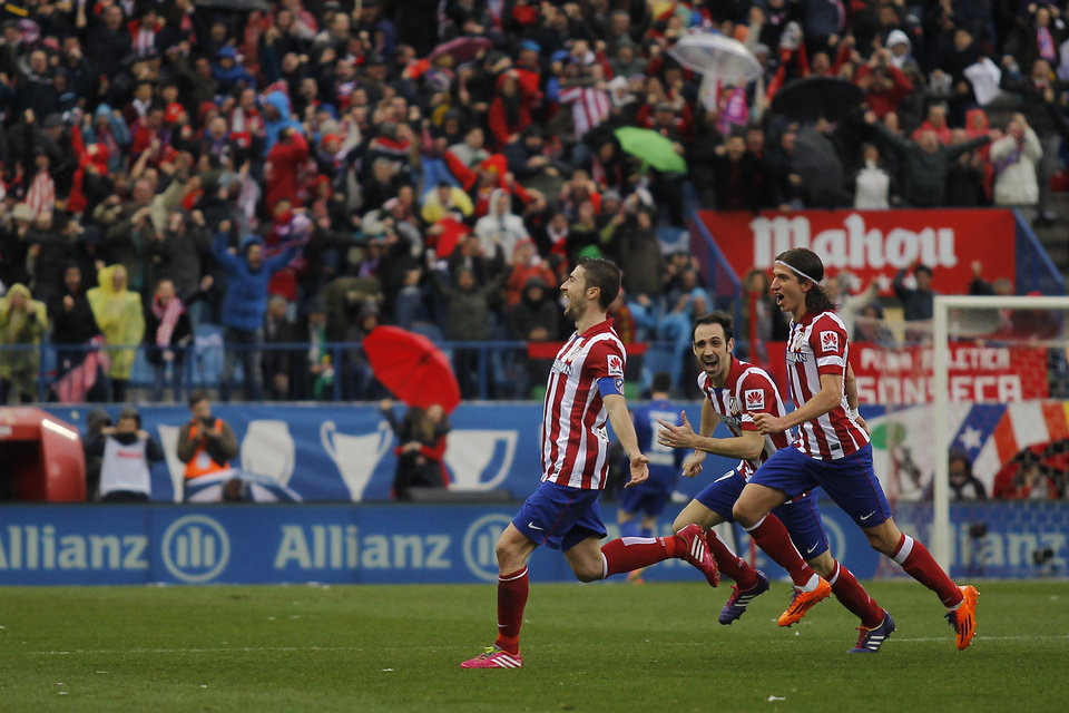Photo - Atletico's Gabi , left, celebrates his goal during a Spanish La Liga soccer match between Atletico de Madrid and Real Madrid at the Vicente Calderon stadium in Madrid, Spain, Sunday, March 2, 2014. (AP Photo/Gabriel Pecot)