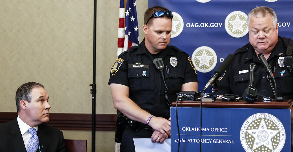 Attorney General Scott Pruitt listens as Norman Police officers Marcus Savage and Sgt. Robert Moore, from left, speak during a ceremony to promote Sexual Assault Awareness Month at the Attorney General's office on Monday, April 8, 2013, in Oklahoma City, Okla.