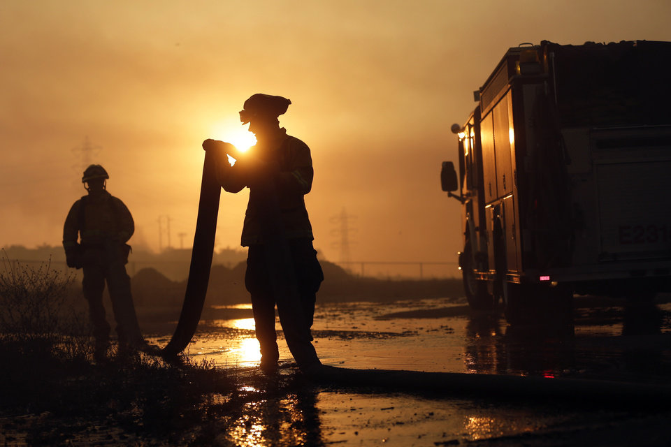 Photo - Del Mar firefighters roll up hose after a day fighting wildfires Wednesday, May 14, 2014, in Carlsbad, Calif. More wildfires broke out Wednesday in San Diego County,  threatening homes in Carlsbad and forcing the evacuations of military housing and an elementary school at Camp Pendleton. (AP Photo)